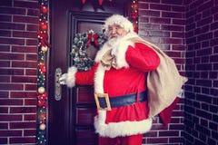 Glade kommande Santa Claus i hemmet för jul Arkivbild
