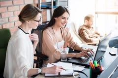 Glade koncentrerade kvinnor som i regeringsställning arbetar arkivfoto