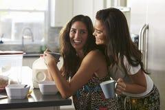 Glade kvinnliga par i deras 20-tal som omfamnar in i köket Arkivbilder