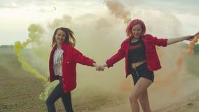 Glade kvinnor i kulör rök som hoppar over ner vägen