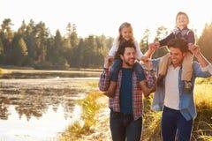 Glade manliga par med barn som går vid sjön royaltyfria foton