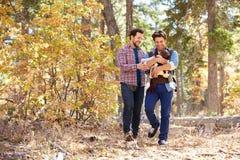 Glade manliga par med behandla som ett barn att gå till och med nedgångskogsmark fotografering för bildbyråer