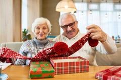 Glade morföräldrar som öppnar julgåvor på tabellen arkivfoton