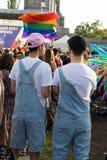 Glade par i en konsert som tycker om stolthetfestivalen i Sofia Homosexuella partners med samma kläder och hattar royaltyfri fotografi