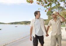 Glade par på semesterinnehavhänder fotografering för bildbyråer