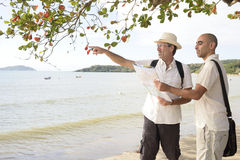 Glade par på semestern som pekar på destinationen Fotografering för Bildbyråer