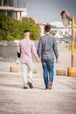 Glade par som går rymma händer arkivfoton
