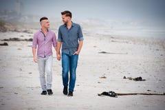 Glade par som går rymma händer royaltyfri fotografi