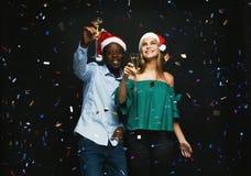 Glade par som gratulerar på jul med champagne på svart bakgrund Royaltyfria Foton