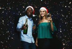 Glade par som gratulerar på jul med champagne på svart bakgrund Royaltyfri Fotografi