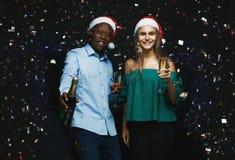 Glade par som gratulerar på jul med champagne på svart bakgrund Arkivfoton
