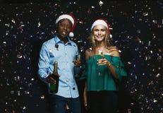 Glade par som gratulerar på jul med champagne på svart bakgrund Arkivfoto