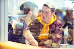 Glade par som tillsammans talar i ett kafé Arkivfoto