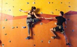 Glade par som upp tillsammans klättrar väggen Royaltyfri Fotografi