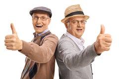 Glade pensionärer som rymmer upp deras tummar Arkivfoton