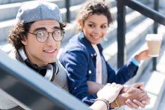 Glade romantiska tonåringar sitter tillsammans på moment arkivbild