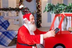 Glade Santa Claus som tycker om med den moderna grejen Royaltyfri Foto