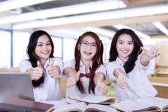 Glade studenter ger upp tummar på kameran Royaltyfria Bilder