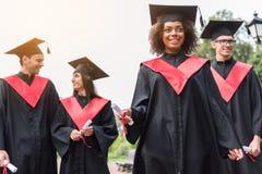 Glade studenter som firar deras avläggande av examen från universitet royaltyfri bild