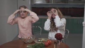 Glade systrar som bedrar runt om coocking av en grönsaksallad som applicerar gurkaskivor till deras ögon som sitter i köket stock video