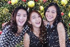 Glade tonårs- flickor med bakgrund för julträd Royaltyfri Foto