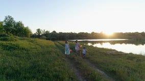Glade tonårs- flickor med ungen med kulöra band och bollar i händer går på den gröna gläntan nära sjön lager videofilmer