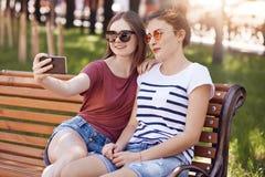 Glade två flickor gör selfieståenden med den moderna mobiltelefonen, sitter nära till varandra på bänk parkerar in, iklädd tillfä royaltyfria bilder