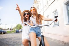Glade unga kvinnor som tillsammans rider en cykel Bästa vän som har gyckel på en cykel på flodpromenaden i citen fotografering för bildbyråer