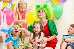 Glade ungar med clownen på födelsedagpartiet royaltyfria foton