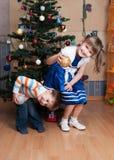 Glade ungar som spelar i en julgran (3 år och 6 år) Arkivfoto