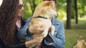 Glade ungdomarspelar med den härliga hunden i parkera som har gyckel och att skratta lockigt nätt flickahår long arkivfilmer