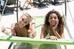 Glade ungdomliga flickor som kopplar av på havet arkivbilder