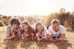 Glade vänner har gyckel tillsammans, använder moderna mobiltelefoner, roliga video för klocka, missbrukas från moderna teknologie Royaltyfri Fotografi