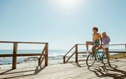 Glade vänner som rider en cykel arkivbilder