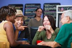 Glade vuxna människor i kafé Arkivfoto