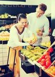 Glade vuxna par som avgör på frukter shoppar in Arkivbilder