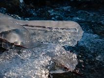 Glades of ice on the banks of a river with a background of mountains royalty free stock photos