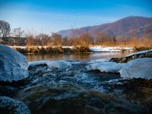 Glades of ice on the banks of a river with a background of mountains royalty free stock image