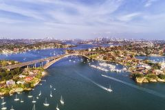 Gladesville bridge across Parramatta river in Sydney`s Inner West with distant view of the city CBD on the horizon. Speed boats stock images