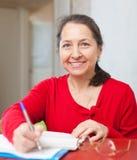 Gladful-Frau füllt Dokumente aus Stockbilder