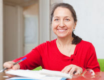 Gladful mature woman fills in documents. At home stock photo