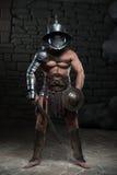 Gladiador en casco y armadura que sostiene la espada Imagenes de archivo