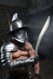 Gladiador en casco y armadura que sostiene la espada Fotos de archivo libres de regalías