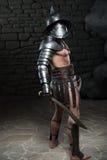 Gladiador en casco y armadura que sostiene la espada Fotos de archivo