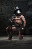 Gladiador en casco y armadura que sostiene la espada Foto de archivo libre de regalías