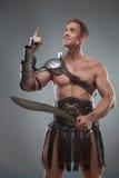 Gladiador en la armadura que presenta con la espada sobre gris Fotografía de archivo