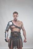 Gladiador en la armadura que presenta sobre fondo gris Imagen de archivo libre de regalías