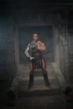 Gladiador en la armadura que se coloca en pasos de antiguo Foto de archivo