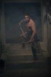 Gladiador en la armadura que se coloca en pasos de antiguo Imagenes de archivo