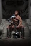 Gladiador en la armadura que se sienta en pasos de antiguo Imagen de archivo libre de regalías